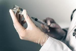 The doctor holding a syringe with Covid-19 vaccines in glass bottle. Covid-19 corona virus treatment concept. photo