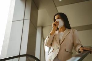 Asian woman wearing N95 mask to protect pollution PM2.5 and virus. COVID-19 Coronavirus and Air pollution pm2.5 concept. photo