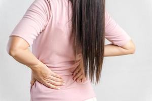 Young woman feeling pain in her back on white background. Healthcare and medical concept. photo