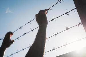 manos de hombre sosteniendo alambre de púas. refugiado, concepto de libertad. foto