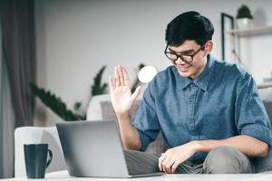 Young Asian man using smartphone for online video conference call waving hand making hello gesture on the couch in living room at night. photo