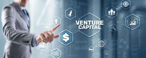 Venture capital. Investor capital. Businessman pressing virtual screen inscription photo