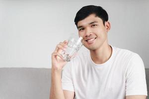 Apuesto hombre asiático bebiendo un vaso de agua en el sofá de la sala de estar foto