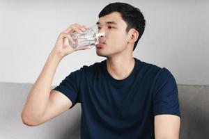 handsome asian man drinking a glass of water on the sofa at living room photo
