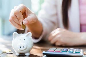 Primer plano de la mano de la mujer de negocios poniendo moneda de dinero en la hucha para ahorrar dinero. Ahorro de dinero y concepto financiero. foto