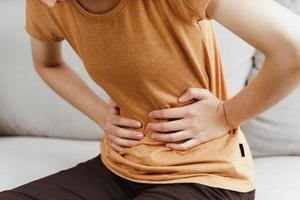 Young woman suffering from strong abdominal pain sitting on the couch at home. Gastritis, Period, menstruation. photo