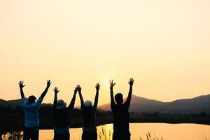 grupo de personas con los brazos levantados mirando al amanecer en el fondo de la montaña. conceptos de felicidad, éxito, amistad y comunidad. foto