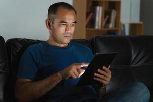 Man sitting on sofa, using tablet computer for work or relax at home. work from home concept. photo
