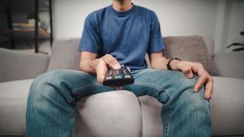El hombre mantenga presionado y presione el botón del control remoto de la TV sentado en el sofá. foto