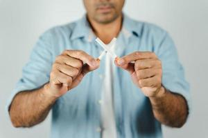 Man hand holding crossed cigarettes. Concept Quitting smoking,World No Tobacco Day. photo