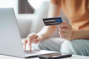 Young woman holding credit card and using laptop computer. Online shopping, internet banking, e-commerce, spending money, working from home concept photo