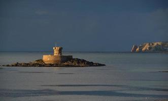 St Ouens Bay Jersey Reino Unido cielos tormentosos sobre la torre rocco del siglo XIX. foto