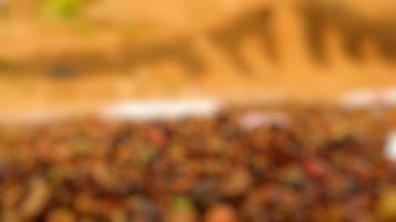 Foto borrosa de granos de café, todavía crudos, secándose al sol