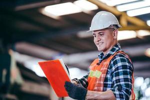 Capataz de fábrica trabajando en el documento en el sitio de construcción foto