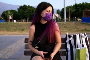 A purple-haired woman with shopping bags. Shopping young woman is resting sitting in the park. She wears a purple mask on his face because of covid 19. photo