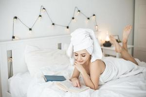 Young happy woman reading paper book in bed. photo