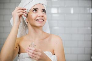 Young woman in white towel apply moisturising oil on face skin. photo