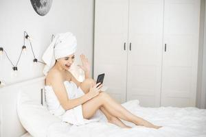 Young woman with towel in white bed video chatting on smartphone. photo