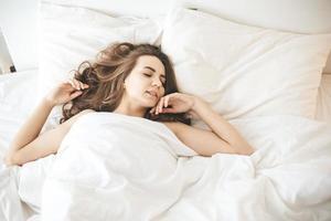 Mujer joven durmiendo pacíficamente en el dormitorio con sábanas blancas frescas foto