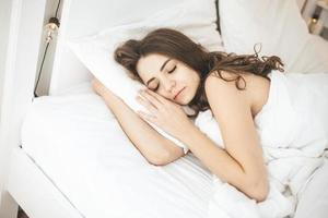 Young woman sleeping peacefully in bedroom with white fresh sheets photo
