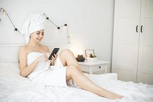 Young woman with towel in white bed texting message on smartphone. photo