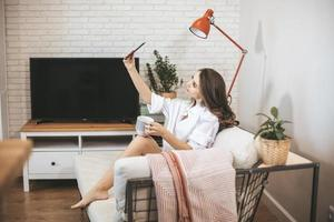 Young woman makes selfie sitting on couch at home. photo