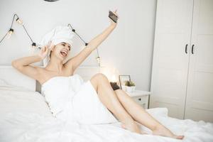 Young woman with towel in white bed taking selfie on smartphone. photo