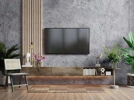 Mockup a TV in modern living room with armchair and plant on concrete wall background. photo