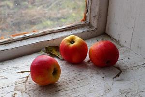 Manzanas rojas en un antiguo alféizar de la ventana foto
