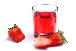 Fresa de frutos rojos y jugo en un vidrio aislado foto
