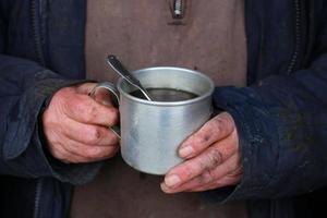 Poor man holding tea to keep warm in winter. photo