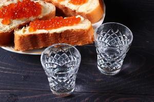 bocadillos con caviar rojo y vodka. foto