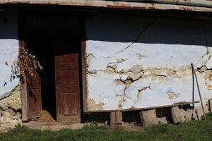 Primer plano de la casa en ruinas de arcilla vieja foto