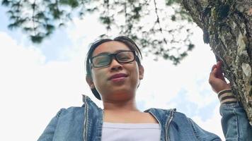 une femme heureuse se tient près d'un arbre majestueux et regarde camara avec un visage souriant par une journée d'été ensoleillée dans le parc. concepts de voyage et de bonheur. video