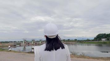 Female engineer in a white helmet reading data in a blueprint and using radio communication at the dam construction site to generate electricity. Clean energy and Technology concepts. video