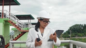 Female engineer in a white helmet working with a digital tablet and looking away at the dam construction site to generate electricity. video