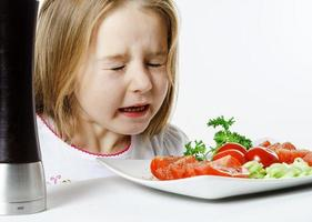linda niña con ensalada y caja de pimiento foto