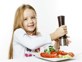 Cute little girl with salad and pepper box photo