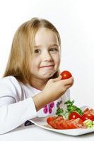 linda niña con plato de verduras frescas foto