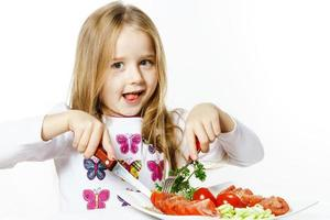 Cute little girl with plate of fresh vegetables photo