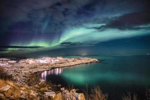 Scandinavian village illumination with northern lights on snow cape photo