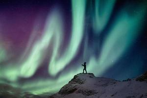 Man climber standing on snowy peak with aurora borealis and starry photo