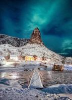 Northern lights over mountain with colors scandinavian village at Lofoten photo
