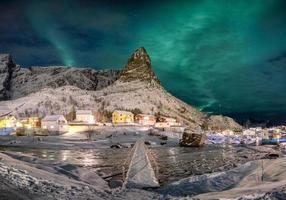 Scandinavian village with aurora borealis over snowy mountain photo