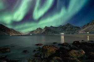 Aurora borealis with stars over mountain range on coastline photo