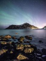 Aurora borealis with stars over mountain with rock on coastline photo