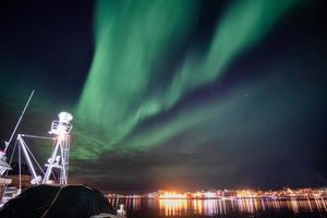 Aurora borealis, Northern lights over illuminated Reine town on coastline at Lofoten Islands photo