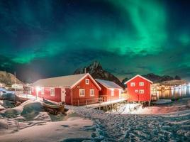 Red house in fishing village with aurora borealis over arctic ocean in winter at night photo