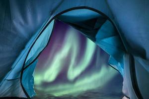 Inside of blue tent camping with aurora borealis flying in the sky photo