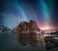 Aurora borealis on mountain in fishing village at Hamnoy photo
